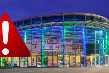 Ein rotes Warndreieck - im Hintergrund: die Joseph von Fraunhoferhalle von außen, bei Nacht