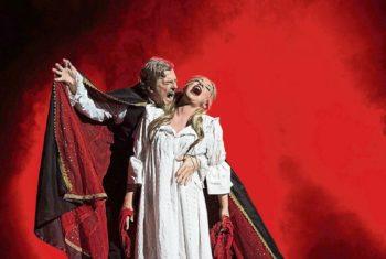 Ein Mann (als Vampir verkleidet) beist einer Frau in den Hals