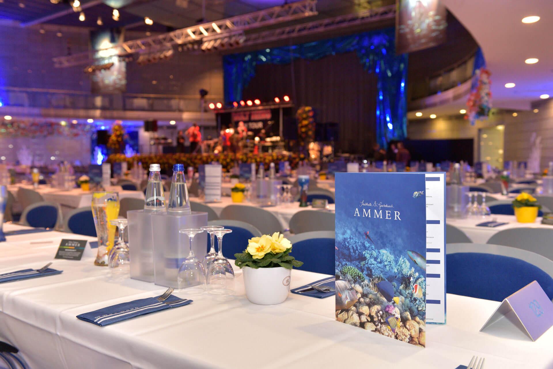 """Eine Speisekarte mit der Aufschrift """"Ammer"""" im Hintergrund die Bühne im Saal"""