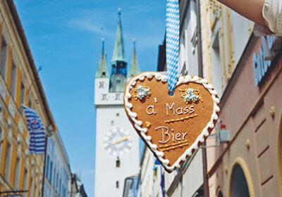 """Ein Lebkuchenherz mit der Aufschrift """"a' Mass Bier"""", im Hintergrund der Stadtturm"""