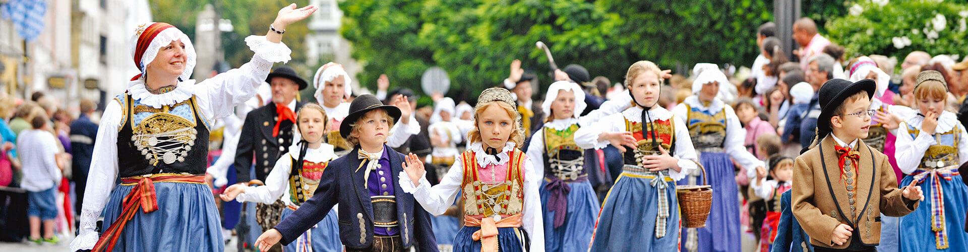 In traditionelle Tracht gekleidete Kinder und Erwachsene beim Festzug