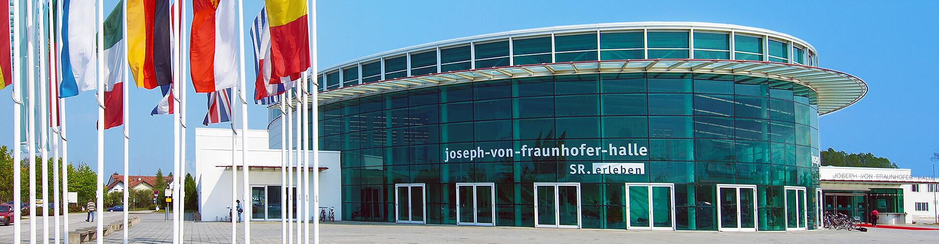 Die Fassade der Joseph von Fraunhoferhalle mit verschiedenen Länderflaggen im Vordergrund