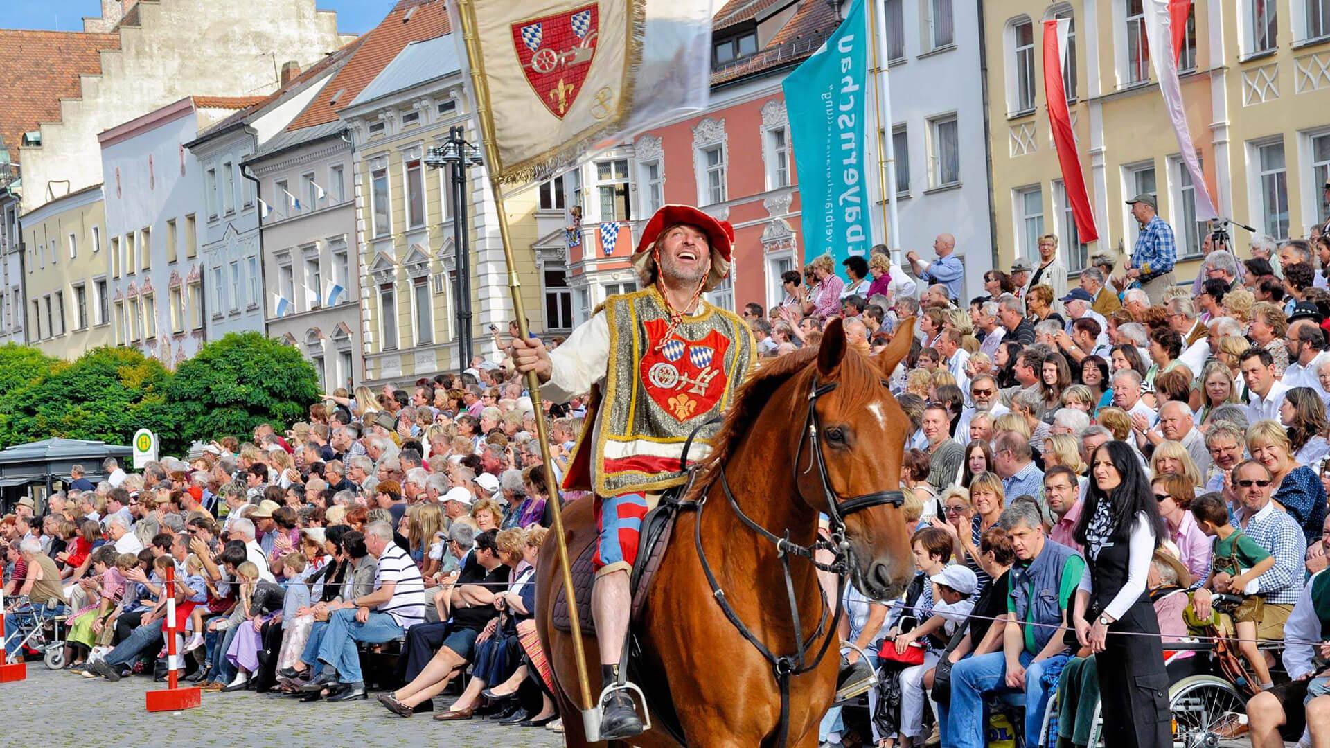 Eine Person reitet mit der Straubinger Flagge