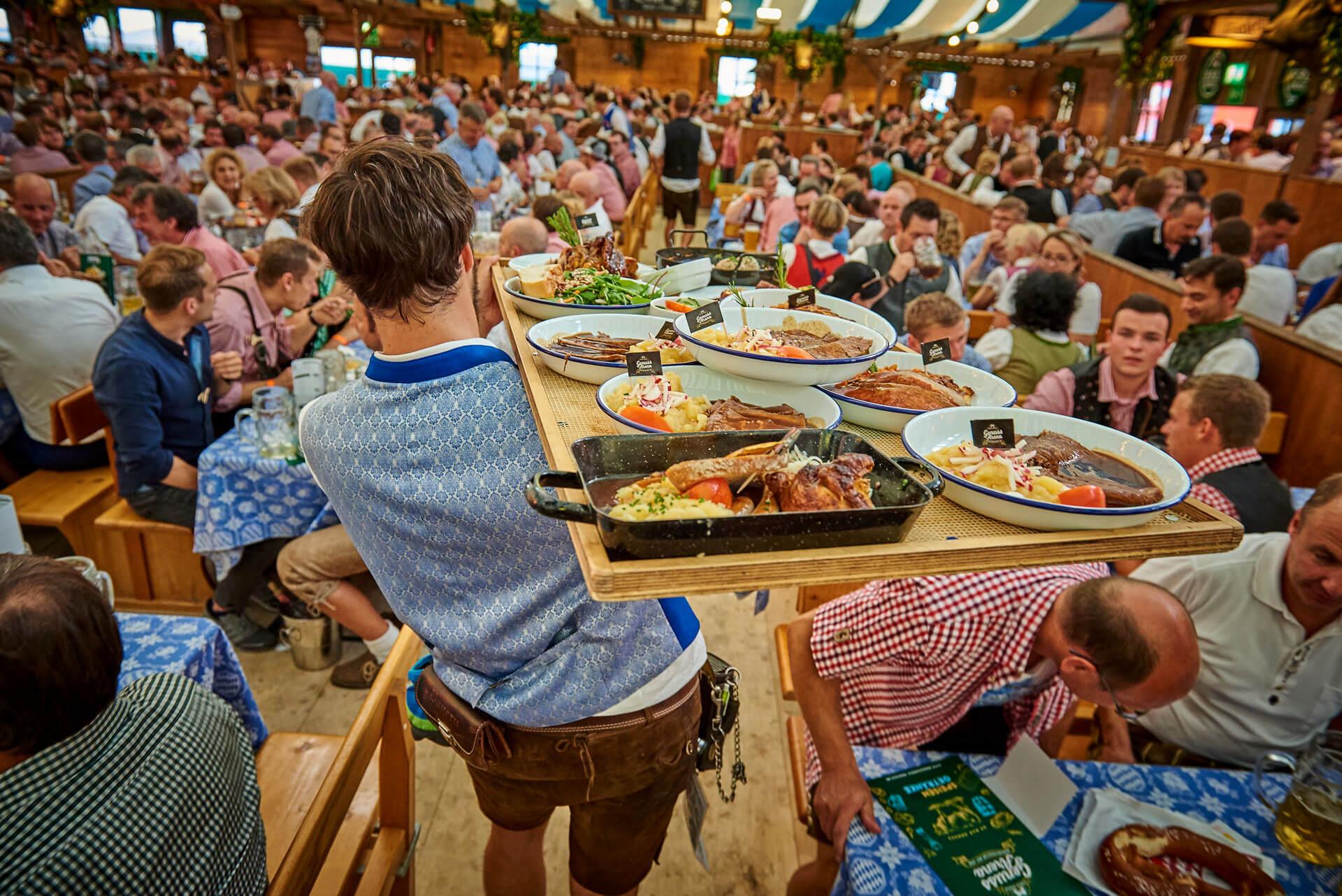 Bedienung trägt verschiedene Gerichte im Bierzelt
