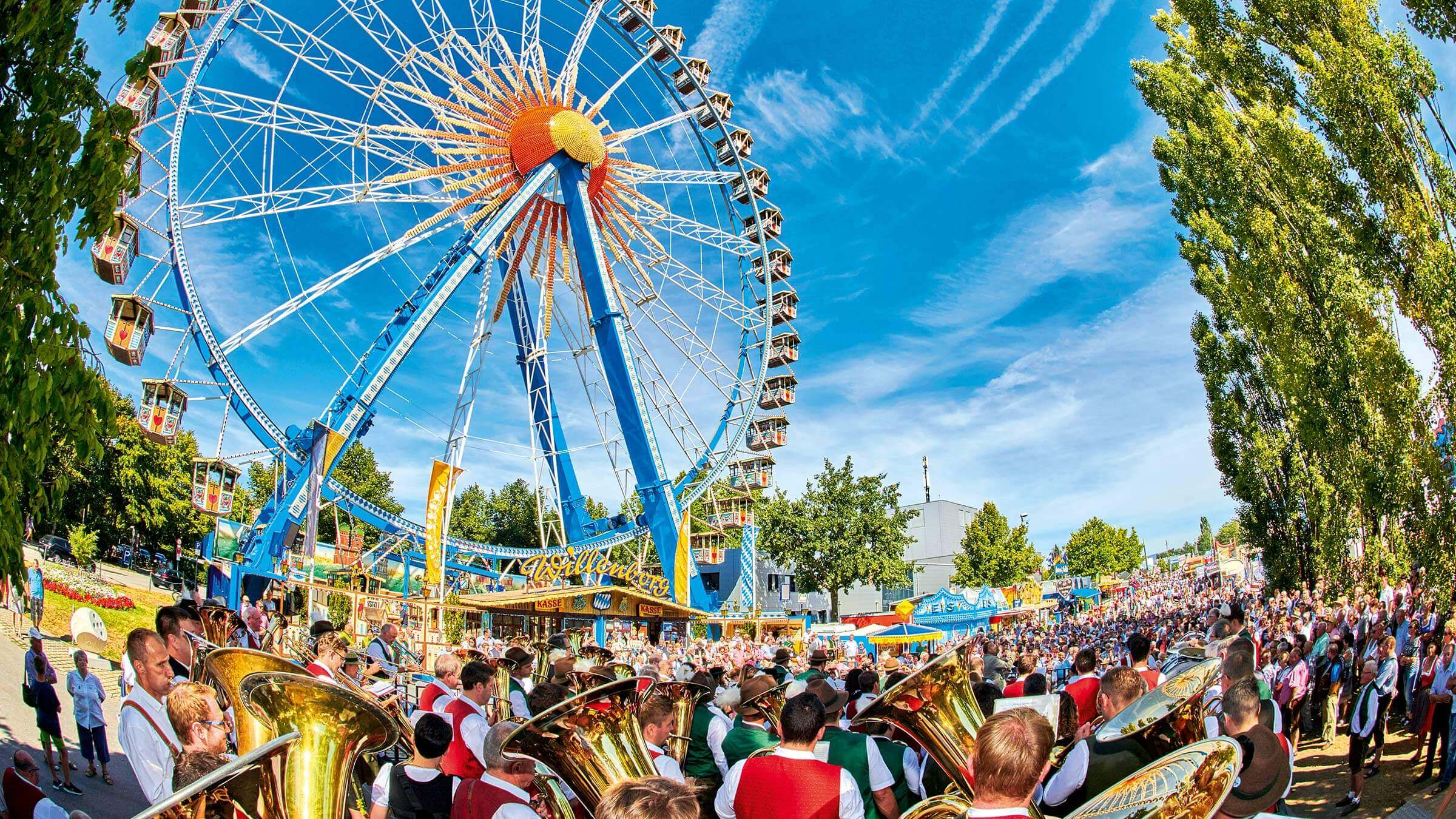Musikanten marschieren auf den Festplatz, im Hintergrund das Riesenrad