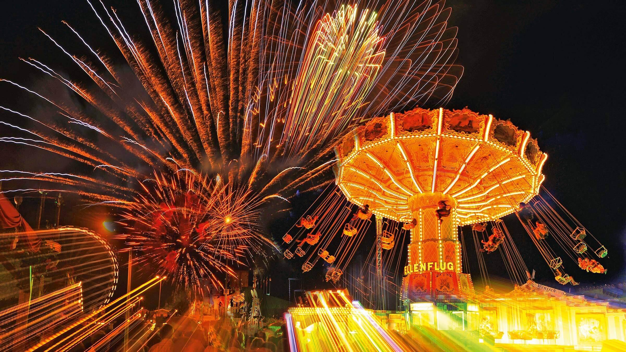 Das Beleuchtete Ketten-Karussell bei Nacht, mit Feuerwerk am Himmel