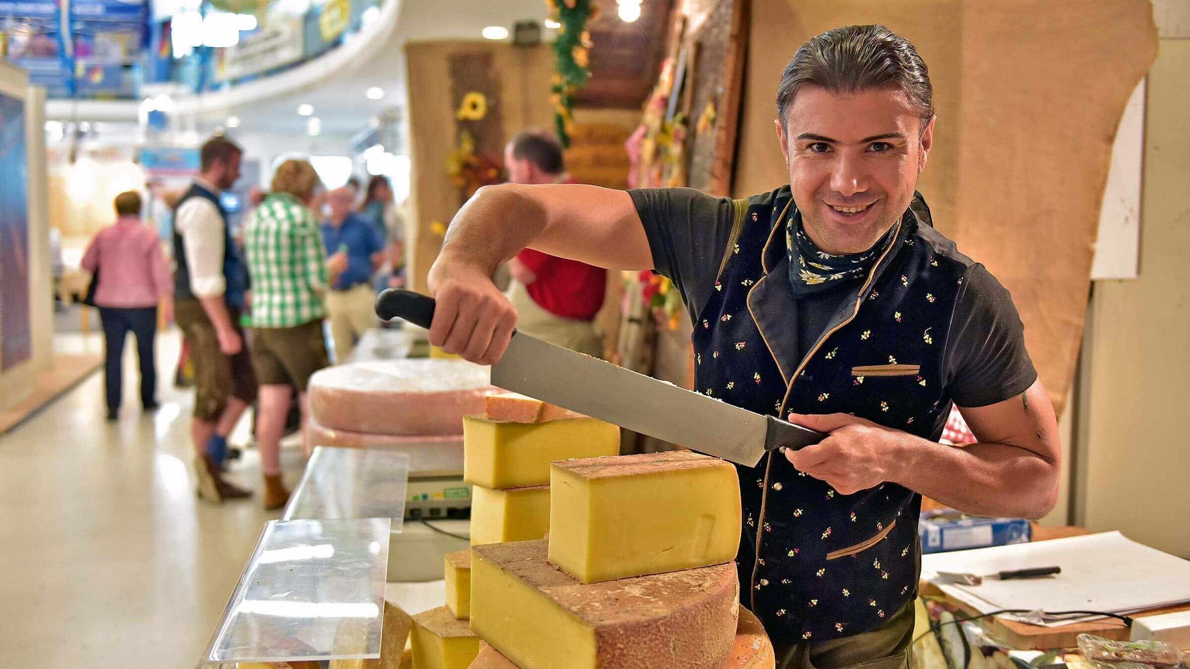 Ein in die Kamera lächelnder Mann schneidet Käse